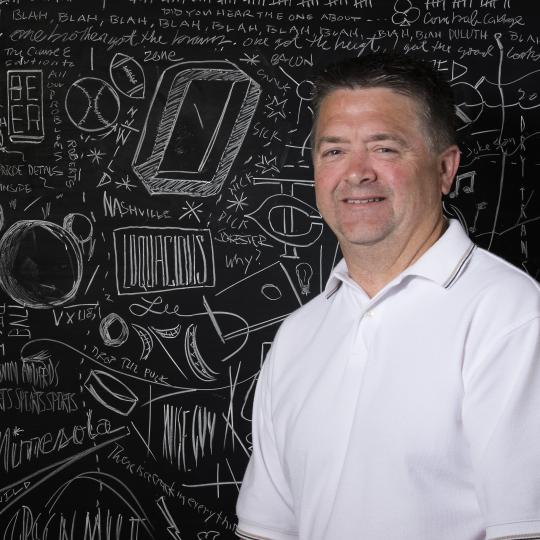 Photo of Chris Magner in front of chalkboard