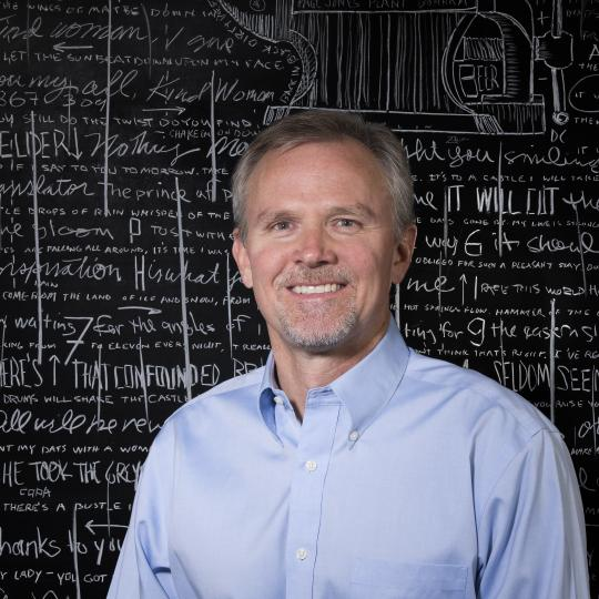 Photo of Paul Hunt in front of chalkboard