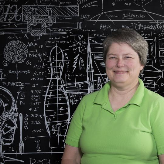 Photo of Tracy Davenport in front of chalkboard